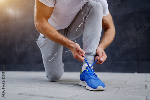 Fotomural Close up of caucasian sportsman in tracksuit tying shoelace while kneeling outdoors
