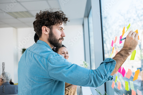 A man writing down on sticky notes stuck on a window.