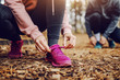 canvas print picture Sporty fit young woman tying shoelace while crouching on trail in nature and getting ready for running. In background her male friend tying shoelace, too. Fitness in nature concept.