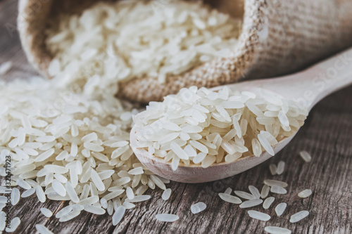 Slika na platnu White rice scattered from a bag on a background of old boards