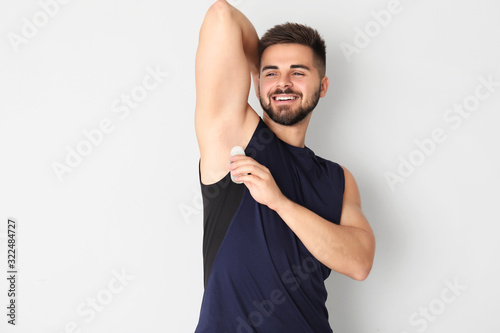 Photo Handsome young man using deodorant on light background