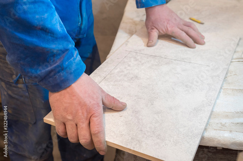 Builder bricklayer installs ceramic tiles. Apartment renovation. Canvas Print