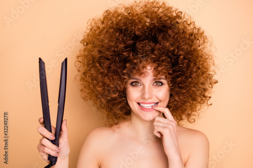 Close-up portrait of nice-looking cute attractive groomed cheerful cheery glad wavy-haired girl holding in hands new professional iron straightener bodycare isolated over beige pastel background