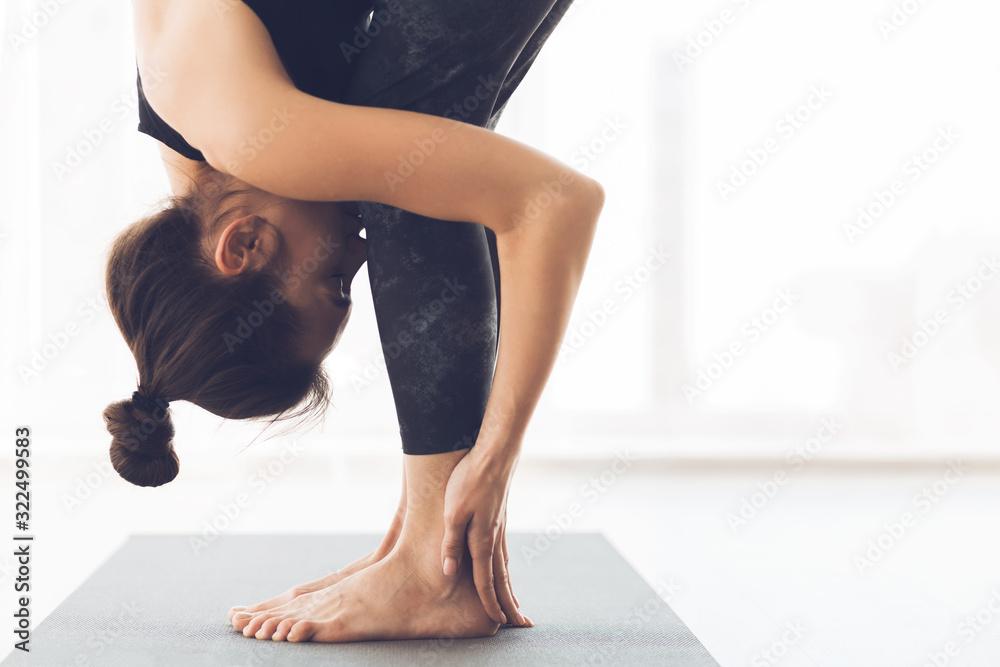 Fototapeta Woman stretching standing in modern light studio