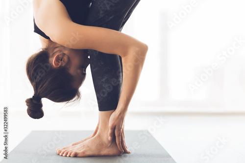 Woman stretching standing in modern light studio Wallpaper Mural