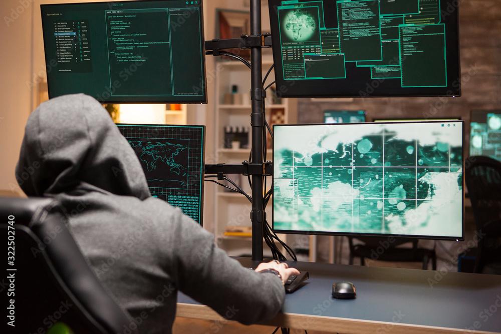 Fototapeta Cyber criminal wearing a hoodie writing a dangerous virus