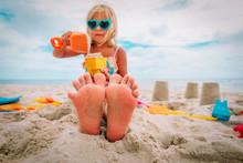 Feet Of Little Girl Play With Sand On Tropical Beach