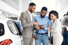 Salesman Offering Couple A Car...