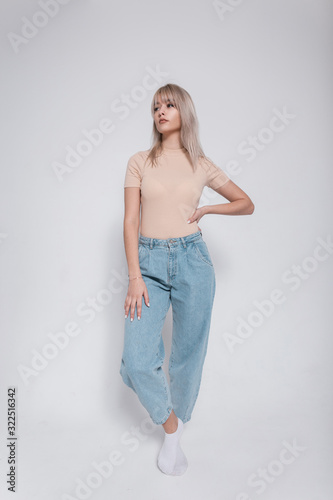 Fashionable young blonde woman in stylish blue jeans in a trendy shirt stands near a white wall indoors. Elegant modern girl fashion model in casual clothes in the studio. Youth modern style. Wall mural