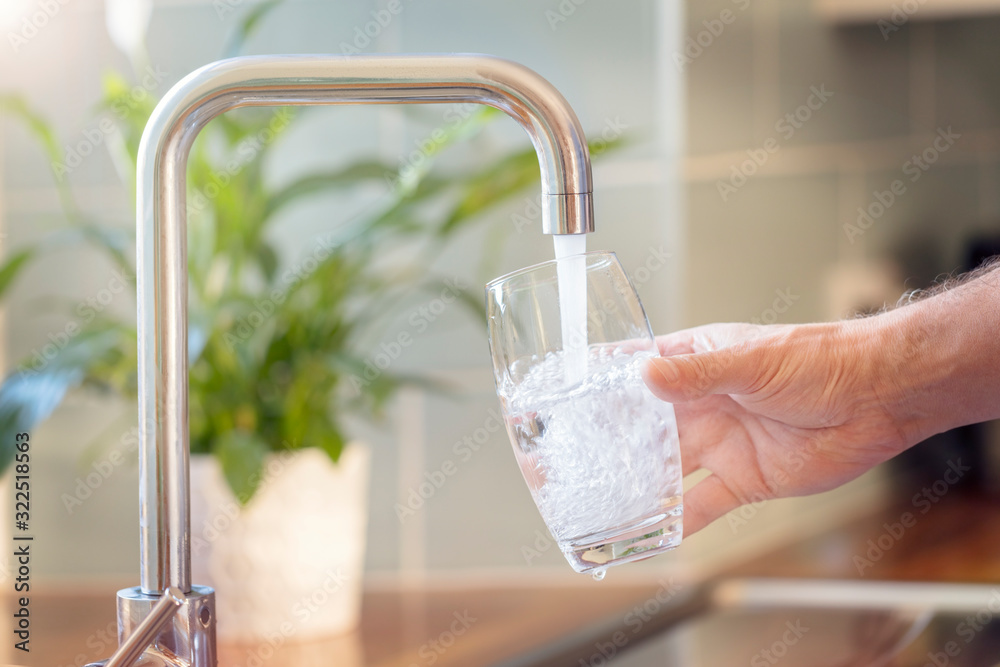Fototapeta Filling up a glass with drinking water from kitchen tap