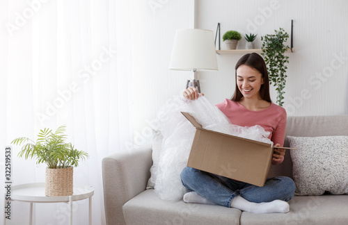 Fototapeta Excited young woman unwrapping parcel, buying goods via internet obraz