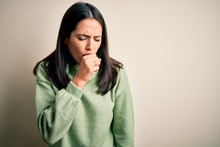 Young Brunette Woman With Blue Eyes Wearing Turtleneck Sweater Over White Background Feeling Unwell And Coughing As Symptom For Cold Or Bronchitis. Health Care Concept.