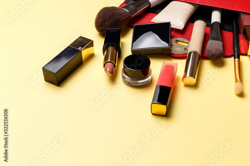 Set of professional elite decorative cosmetics for makeup on a yellow background. The concept of beauty and fashion. A red makeup bag with cosmetic beauty products: lipstick, eye shadow, foundation
