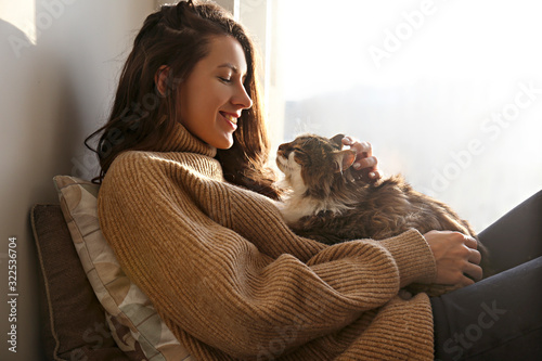 Portrait of young woman holding cute siberian cat with green eyes Tableau sur Toile