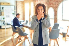 Middle Age Beautiful Businesswoman Wearing Jacket And Glasses Standing At The Office Shocked Covering Mouth With Hands For Mistake. Secret Concept.