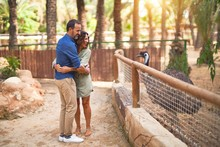 Middle Age Beautiful Couple Smiling Happy And Confident At Town Park. Standing With Smile On Face And Hugging Looking At Emu