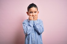 Young Little Boy Kid Wearing Elegant Shirt Standing Over Pink Isolated Background Looking Stressed And Nervous With Hands On Mouth Biting Nails. Anxiety Problem.