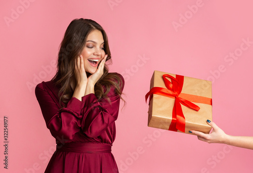 Photo Excited young woman in evening dress getting surprise gift box