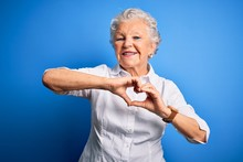 Senior Beautiful Woman Wearing Elegant Shirt Standing Over Isolated Blue Background Smiling In Love Doing Heart Symbol Shape With Hands. Romantic Concept.