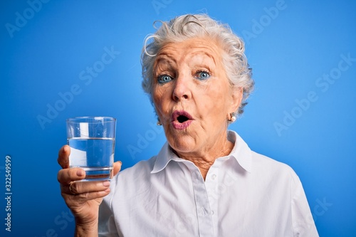 Leinwand Poster Senior beautiful woman drinking glass of water standing over isolated blue backg
