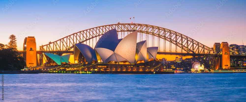 Fototapeta AUSTRALIA - AUGUST 12, 2019: Cityscape panorama view of Opera house with blue sky. The most famous tourist attraction in Sydney city, Australia.