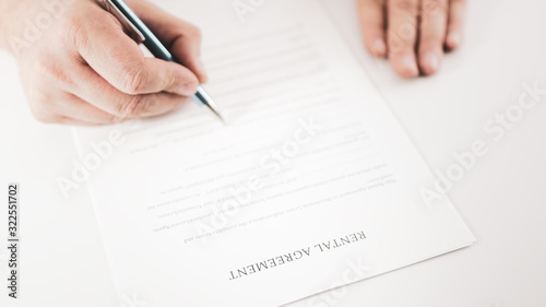 Photo Closeup of a businessman  signing a rental agreement with a pen.