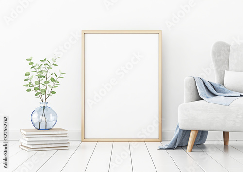 Poster mockup with vertical frame standing on floor in living room interior with armchair and branches in blue vase on empty white wall background Tablou Canvas