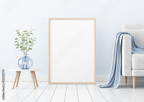 Photo Poster mockup with vertical wooden frame standing on floor in living room interior with sofa and branches in blue vase on empty wall background