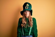 Beautiful Brunette Woman Wearing Green Hat With Clover Celebrating Saint Patricks Day Making Fish Face With Lips, Crazy And Comical Gesture. Funny Expression.