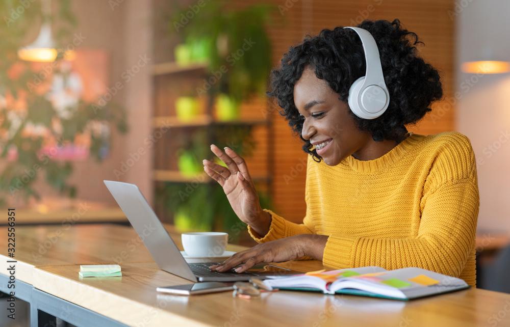 Fototapeta Afro girl in headset using laptop, having skype conference