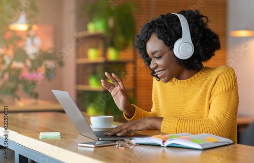 Obraz Afro girl in headset using laptop, having skype conference - fototapety do salonu