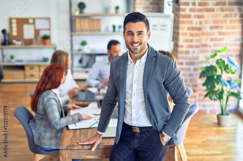 Obraz Group of business workers working together. Young handsome businessman standing smiling happy looking at the camera at the office - fototapety do salonu
