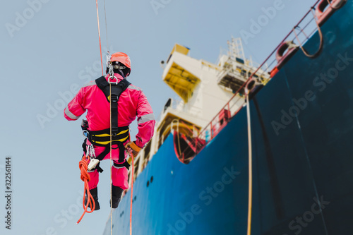 Abseiling, rope access Worker on the high place scaffolding wear equipment protective safety harness in shipyard at side shell of hull vessel repair on accommodation bridge deck background Wallpaper Mural