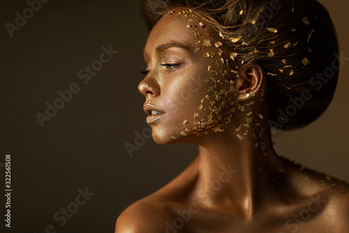 Fashion art portrait of model girl with holiday golden shiny professional makeup. beaty woman with gold metallic body and hair on dark background. Gold glowing skin. copy space
