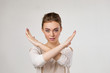 canvas print picture - beautiful young woman making stop gesture on gray background.