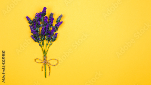 one twig of a lavender flower tied up with a thread and bow on a yellow background. copy space for design ideas