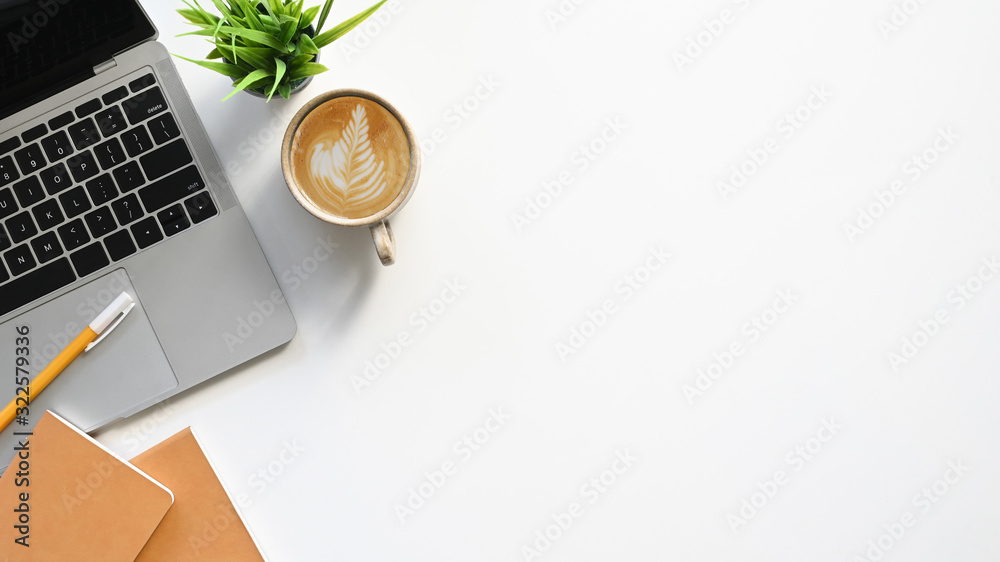 Fototapeta Top view of white working table with office equipment putting on it. Flat lay Computer laptop, Coffee cup, Potted plant, Notebook and pencil. Modern and comfortable working desk concept.