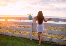 Back View Brunette Girl Luxury Long Hair, Transparent Sexy Dress. Backdrop Sunny Bright Yellow Sunset Wooden Fence. Sea Ocean Vacation. Tourist Enjoy Sun Shine Summer. Art Fantasy Nature Georgia