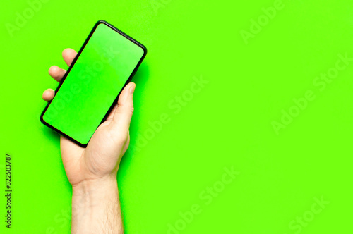 Male hands hold a modern black smartphone with green blank screen on neon green background flat lay top view. Modern technology, phone, gadget in hands, touch screen, template for your design. Mockup