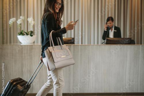 Fototapeta Business traveler in hotel hallway with phone