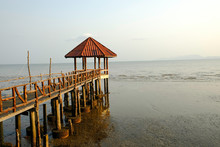 Old Bridge To Building Red Roof On Black Sand Beach At Thailand