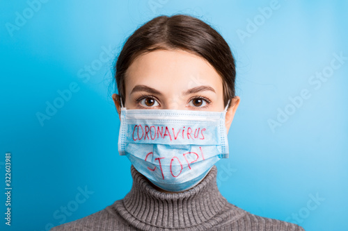 Obraz Portrait of a woman in medical mask with stop coronavirus text at blue background. Coronavirus concept. Respiratory protection - fototapety do salonu