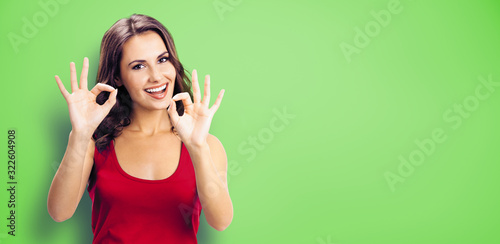 Young happy smiling beautiful woman in casual clothing, showing okay gesture, or zero hand sign, green color wall background Canvas Print