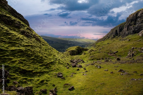 Beautiful shot of the green valley in the mountains full of stones during sunset
