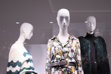 Three Or A Group Of Female Bald White Mannequins In A Shop Window. Mannequins Are Dressed In Dresses, Sweaters, A Fur Coat, Jewelry.
