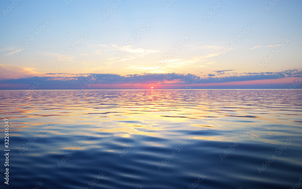 Fototapeta Colorful sunset sky above the Baltic sea, Latvia. Sunlight through the clouds, reflections on the water