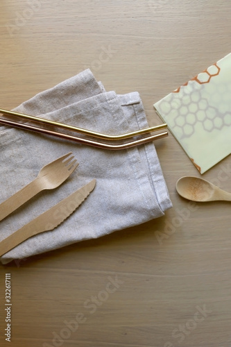 Photo Linen cloth, reusable straws, wooden cutlery and beeswax wrap on a wooden table
