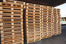 The Multiple Stacks Of Wooden Pallets In The Stock