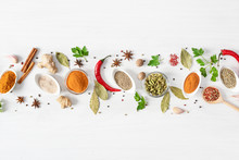 Various Assorted Colorful Spices And Herbs On White Wooden Background Top View.