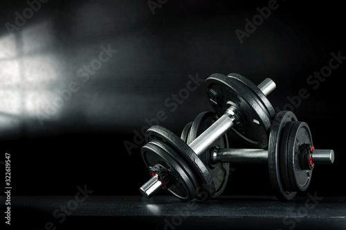 Fototapeta Dark interior of gym with shadow of window and dumbbells on desk.  obraz